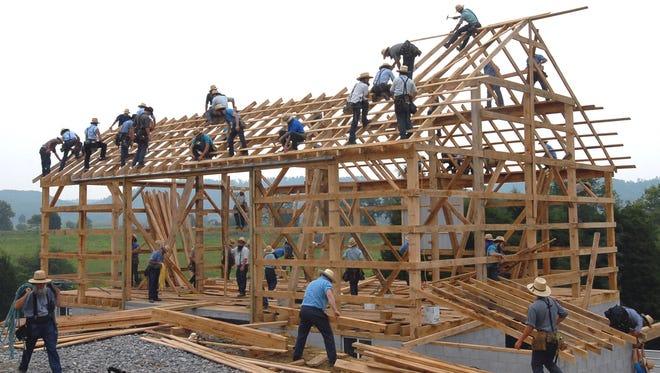 Image of Mennonites building a barn.